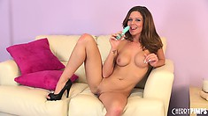 Sweet looking brunette Kimber Peters toys her cunt hole on the couch