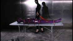 Latex slave gets bound to a table and beaten by her sexy mistress