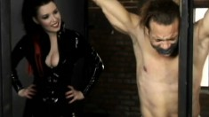 Mistress Anastasia Pierce ties her slave up to bars and punishes him