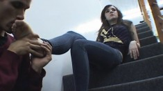 Beautiful brunette has a lustful dude licking her feet on the stairs