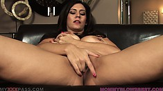 Stacked brunette milf with a big round ass sits on the couch fingering her cunt