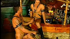 Three ripped playboys wearing leather straps ream each other's butts